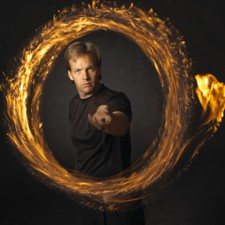 Comedy Juggler Paul Isaak, surrounded by a ring of fire, during a stage show